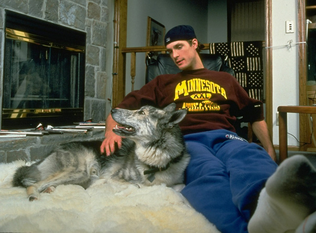 Christian Laettner and Chief relax by the fireplace at the forward's Minneapolis home.