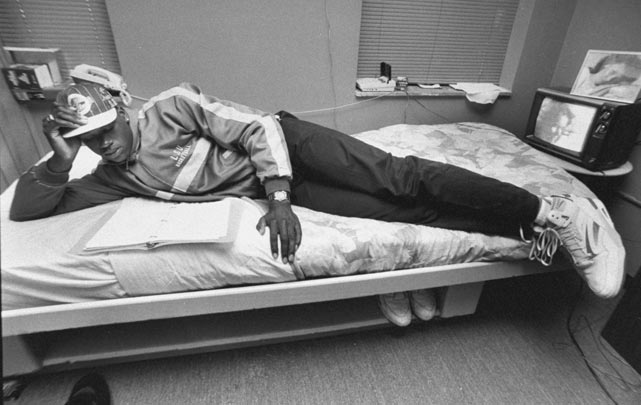 Shaquille O'Neal tries to fit his 7-foot-2 body on an undersized dorm bed.