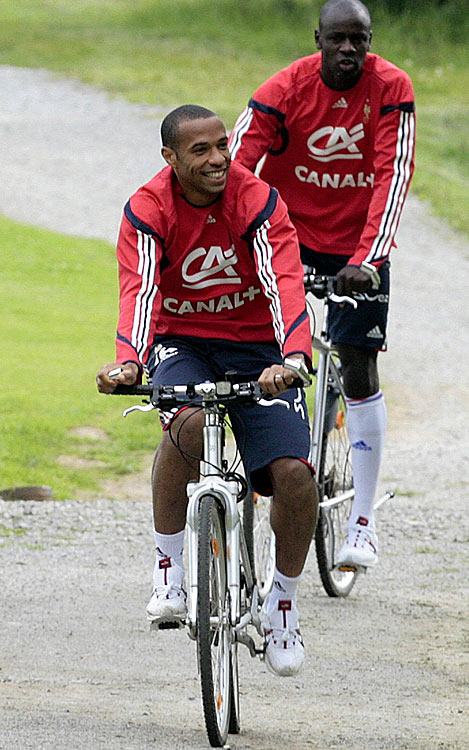 Henry (front, with French soccer teammate Lilian Thuram) ride near their hotel in Arzen, Germany, during the 2006 World Cup.