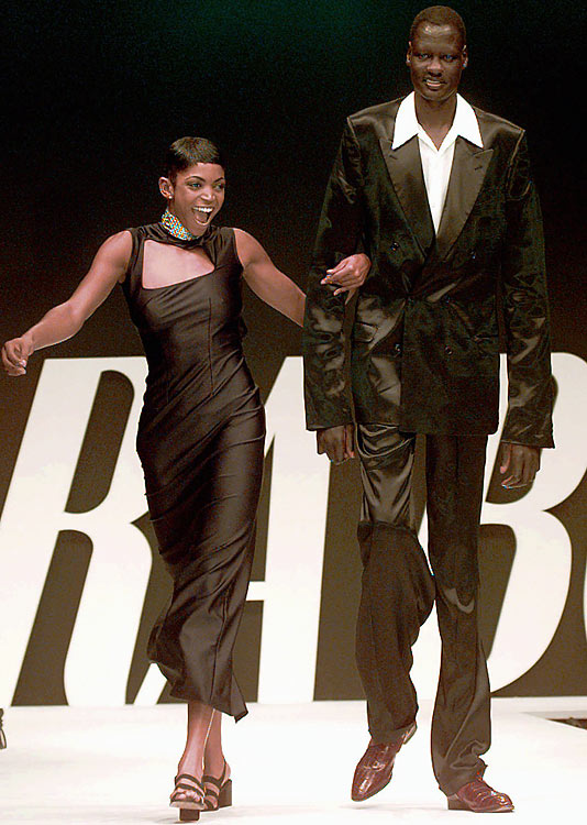 Though his playing career was over, Bol was not out of the spotlight. In this photo, he accompanies U.S. volleyball star Keba Phipps on the on the catwalk at the unveiling of her fashion collection in Milan.
