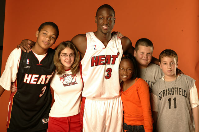 Wade poses with some Miami area children during a SI for Kids photo shoot.