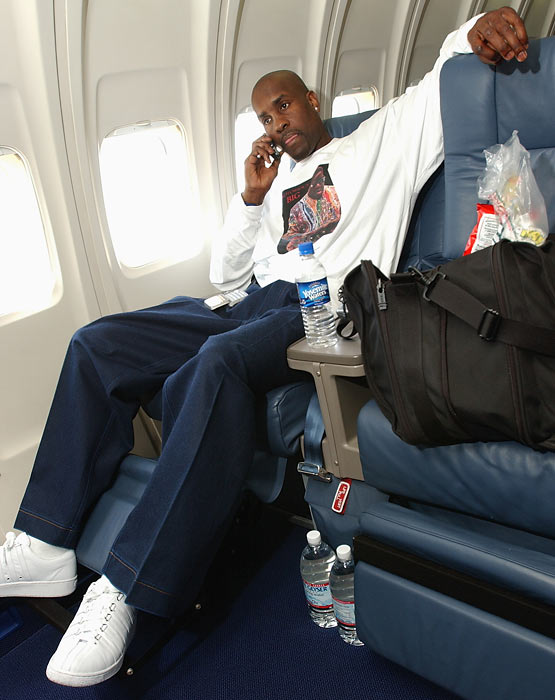 Gary Payton makes a call while on the team plane before Game 1 of the Western Conference Finals during the 2004 NBA Playoffs.