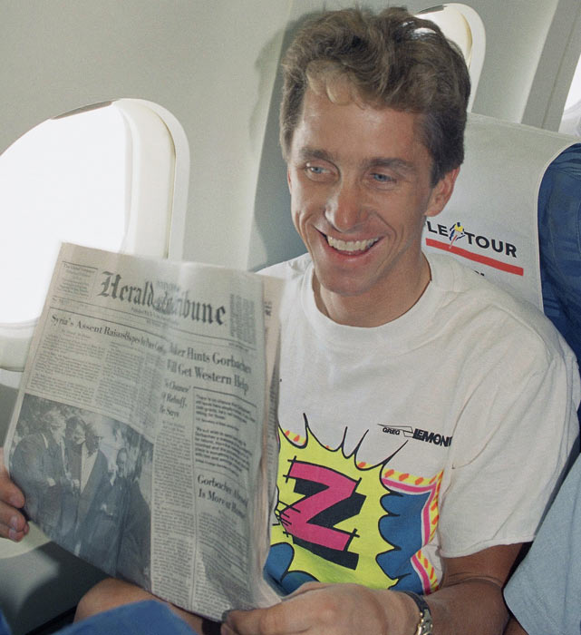 Greg LeMond folds his newspaper upon his arrival at Pau airport, where he arrived along with other riders for the Tour de France.