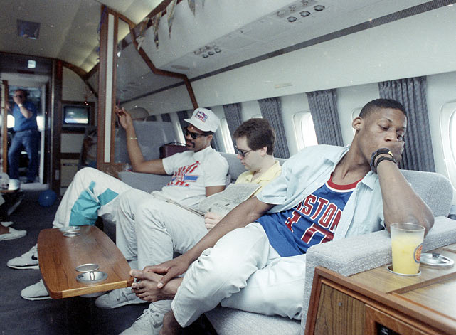 A subdued Dennis Rodman relaxes aboard a private jet as his team prepares to return home from Los Angeles. James Edwards is pictured in the background.