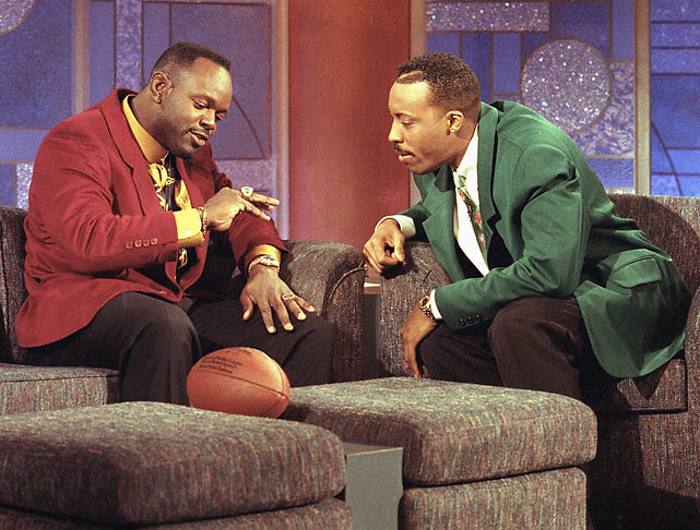 After leading the Cowboys to a victory in Super Bowl XXVII, Smith shows off his championship ring to Arsenio Hall.