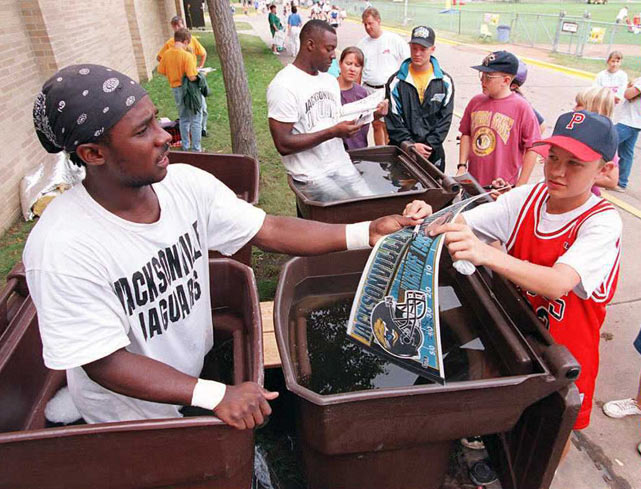 Former Heisman Trophy winner Desmond Howard (left) and teammate Willie Jackson (center) sign autographs while standing in trash cans filled with ice water during training camp for the expansion Jaguars at the University of Wisconsin-Stevens Point campus.