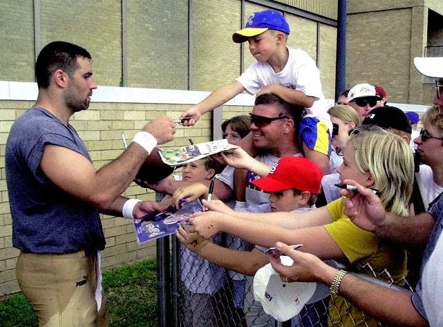 St. Louis quarterback Kurt Warner signs autographs following the Rams' practice at training camp at Western Illinois University in Macomb, Ill.