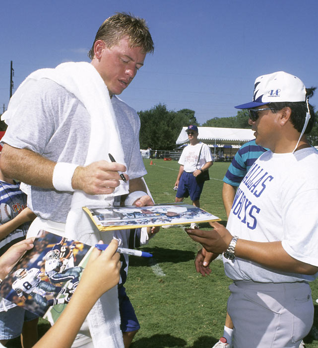 Dallas' Troy Aikman signs autographs for fans at Cowboys camp in Austin, Texas.