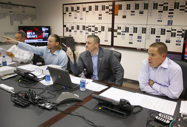 Denver Broncos director of college scouting Matt Russell (left) and general manager Brian Xanders (center) point out a player on the board as head coach Josh McDaniels (right) listens  during the first round of the NFL Draft at Dove Valley headquarters in Englewood, Colo. The Broncos selected Florida quarterback Tim Tebow with the 25th overall pick.