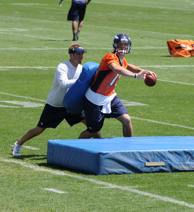 Former Broncos quarterbacks coach Ben McDaniels pushes Tebow during a passing drill in 2010. Ben was let go by the Broncos when his brother, Josh, was fired as head coach following the 2010 season.