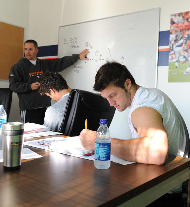 Tebow takes notes at a 2010 quarterbacks meeting with former Broncos' head coach Josh McDaniels. McDaniels is currently the offensive coordinator for the St. Louis Rams.