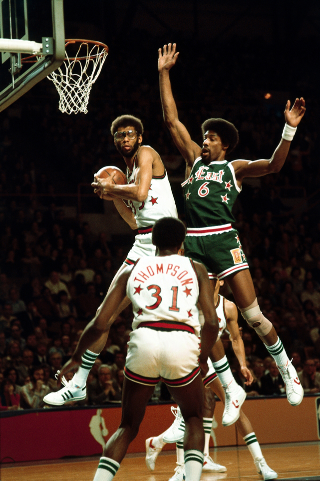 Kareem Abdul-Jabbar grabs a board in front of Julius Erving. Dr. J and the East team were wearing green in honor of the hometown Bucks.