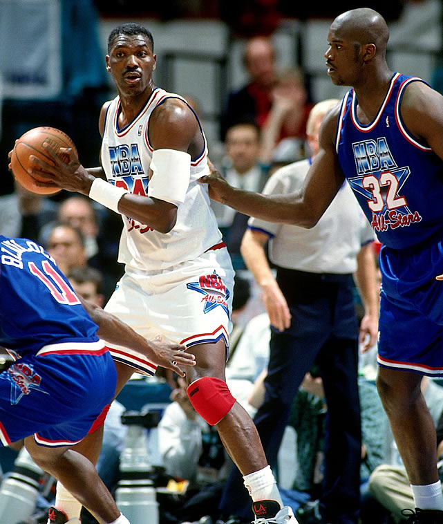 Hakeen Olajuwon posts up a young (and pretty in-shape) Shaquille O'Neal. And that's Mookie Blaylock playing some D in the foreground.