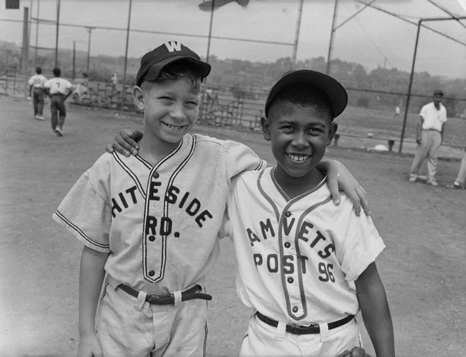 Two Little League baseball players, including one wearing Whiteside Road uniform, and Gary Henderson in Amvets Post 96 uniform, standing on playing field, c. 1953–1956