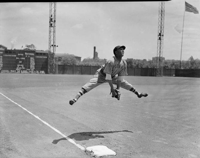 New York Cubans baseball player Horacio Martinez leaping above third base at Forbes Field , 1941