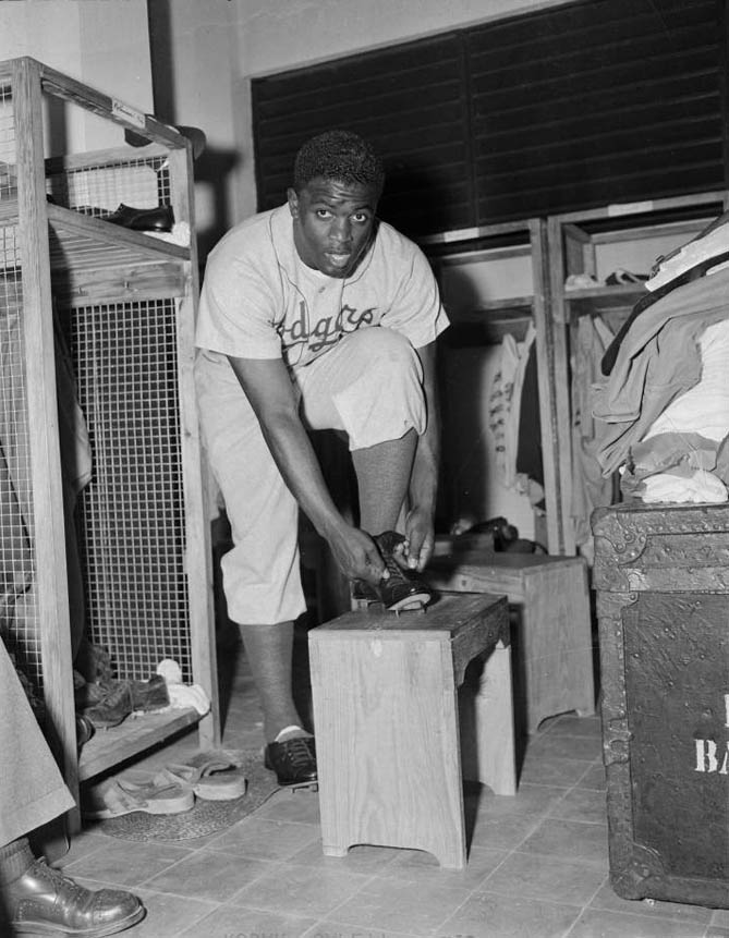 Brooklyn Dodgers baseball player Jackie Robinson tying spikes in locker room, c. 1947