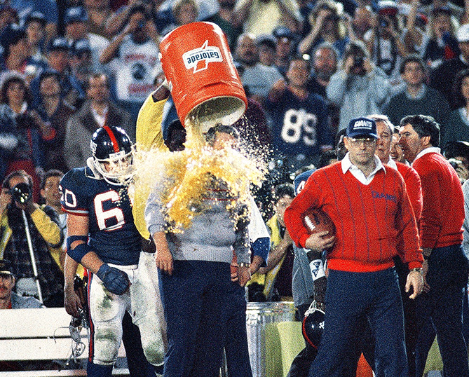 There are 10 seconds left on the clock. You see the players creep up behind their coach with a sly look on their faces. Then, splash! There goes the Gatorade. It's a tradition mostly practiced in football that originated back in 1984, when Chicago Bears Dan Hampton, Steve McMichael, and Mike Singletary teamed up to give coach Mike Ditka a bath in the waning moments of a division-clinching win over the Vikings. It wasn't repeated until the following October, when New York Giants defensive lineman Jim Burt orchestrated a dousing for his coach, Bill Parcells, after a win over the Washington Redskins. It was a way to celebrate, but Burt may have also been looking for a little payback. Parcells had tried to motivate Burt the week before by telling him that he had no chance against the Redskins' offensive line. The Gatorade dump turned into a good-natured tradition for the Giants and Parcells, with Burt and linebacker Harry Carson (right, dunking Parcells after the Giants beat the Broncos in Super Bowl XXI) doing most of the heavy lifting.