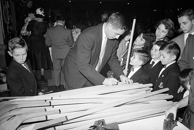 Even before breaking out in the NHL, Beliveau was a fan favorite — especially with kids. Here, Beliveau is autographing hockey sticks at an unidentified banquet event.