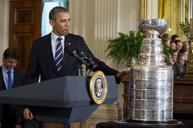 President Barack Obama touches the Stanley Cup as he arrives for a ceremony to honor the NHL champion Chicago Blackhawks,  Monday, Nov. 4, 2013, in the East Room of the White House in Washington.