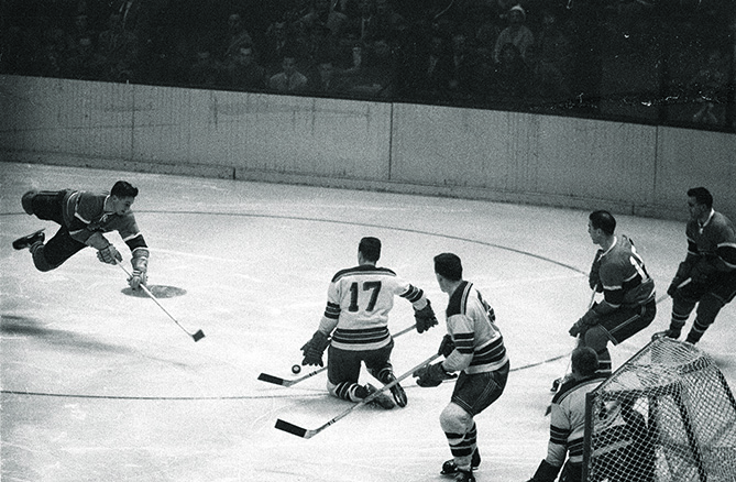After playing three games during the 1952-53 season, Beliveau entered the NHL for good as a center for the Montreal Canadiens in 1953-54. Here, he flies through the air after being tripped during game versus the NY Rangers.