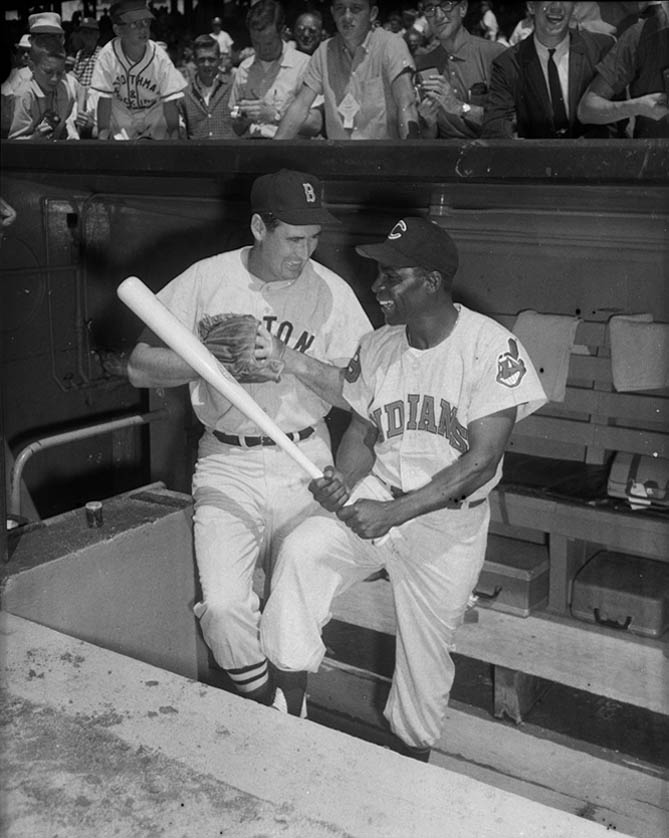 Boston Red Sox baseball player Ted Williams and Cleveland Indians player Minnie Minoso, posed with glove and bat in dugout for 1959 All Star Game, Forbes Field, July 1959