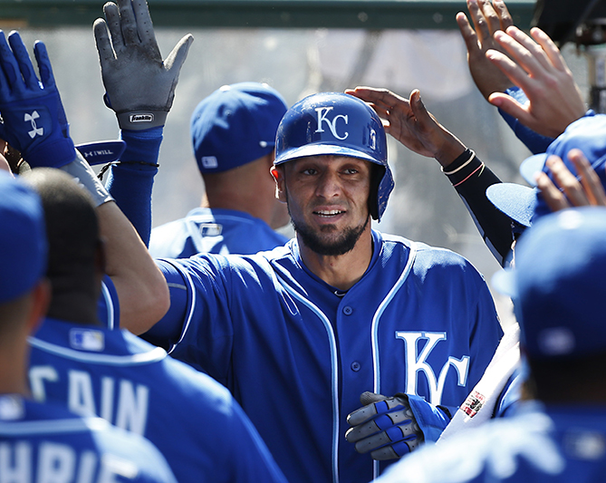 Kansas City Royals' Paulo Orlando is congratulated in the dugout after scoring on a double by Omar Infante in the seventh inning against the Los Angeles Angels in a baseball game in Anaheim, Calif.  Sunday, April 12, 2015. The Royals won 9-2.