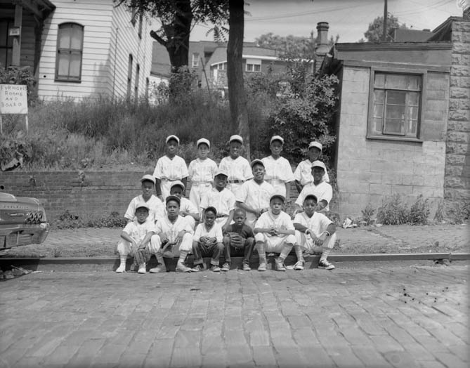Group portrait of sixteen boys, all but two in Astros baseball team uniforms, gathered on curb of Belgian block street, with houses in background, 1965