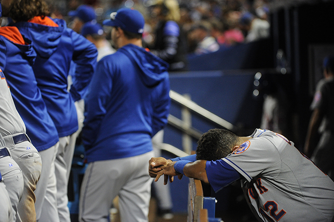 New York Mets center fielder Juan Lagares, right, is seen in the dugout as the eighth inning of a baseball game winds down against the Atlanta Braves, Saturday, April 11, 2015, in Atlanta.