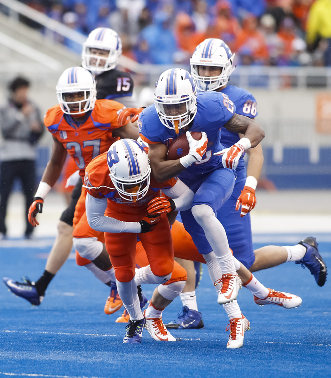 Boise State running back Devan Demas carries the ball past cornerback Raymond Ford the team's NCAA college spring football scrimmage in Boise, Idaho, Saturday, April 11, 2015.