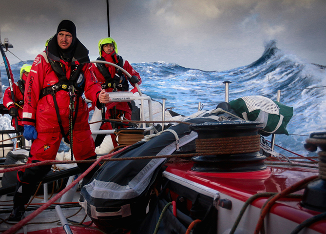 March 23, 2015. Leg 5 to Itajai onboard Dongfeng Race Team. Day 5. Martin Stromberg, Eric Peron and Liu Xue 'Black' on watch with Southern Ocean waves in the background.