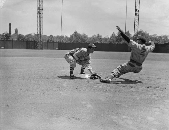 Two New York Cubans baseball players, infielder and runner, no. 2, simulating put out on second base at Forbes Field, 1941
