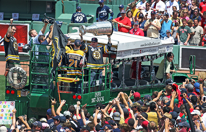 The Bruins Mark Recchi hoists the Stanley Cup to the cheering fans as he and some teammates ride a duck boat towards the right field corner at Fenway Park. The Boston Red Sox hosted the Milwaukee Brewers in interleague MLB action at Fenway Park.