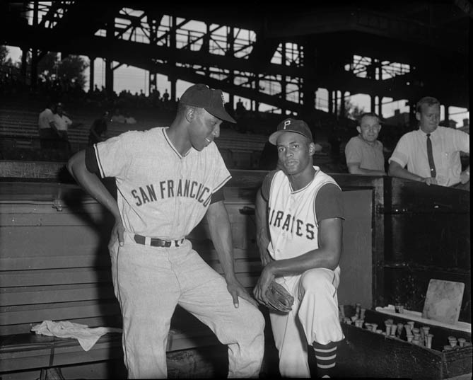 San Francisco Giants baseball player Willie McCovey with Pittsburgh Pirates player Roberto Clemente, posing in front of dugout at Forbes Field, c. 1960