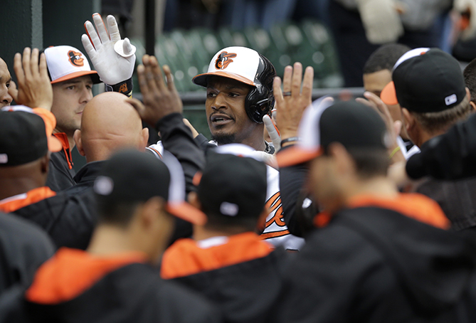 Baltimore Orioles' Adam Jones, center, high-fives teammates in the dugout after hitting a solo home run in the first inning of a home opener baseball game against the Toronto Blue Jays, Friday, April 10, 2015, in Baltimore.