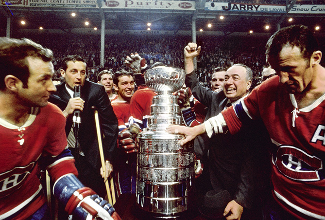 The Canadiens won the 1968 Stanley Cup by defeating the St. Louis Blues. Coach Toe Blake (second from right) celebrates his last Cup win as Beliveau (on crutches) speaks to Montreal Forum crowd.
