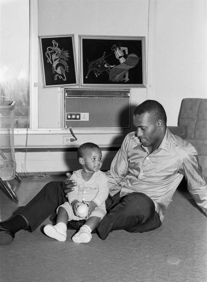 Roberto Clemente and his son Roberto Clemente Jr. seated on floor, in their apartment in East Liberty, June 1966
