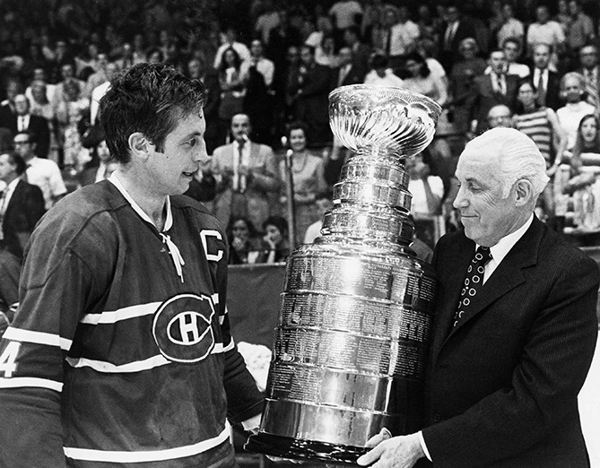 Montreal Canadiens' captain Jean Beliveau is presented the Stanley Cup by NHL Commissioner Clarence Campbell after Montreal beat Chicago in Game 7 of the Stanley Cup Finals. It was his tenth, and final, Stanley Cup.