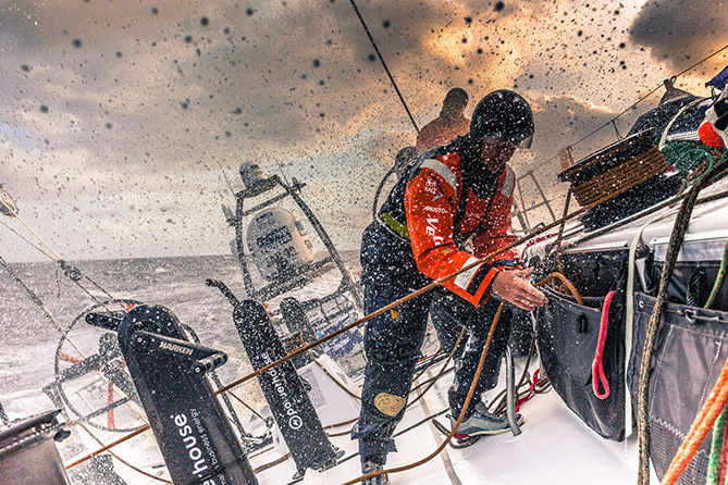 October 24, 2014. Onboard Team Vestas Wind. Nicolai Sehested cleans the cockpit up as waves break over.