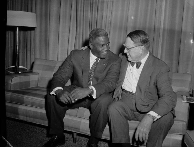 Baseball executive Branch Rickey and baseball player Jackie Robinson seated on sofa in hotel, June 1957