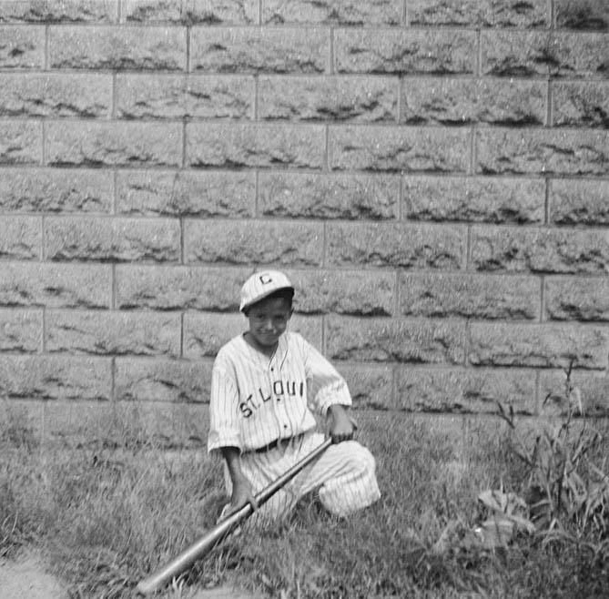 "Portrait of Charles A. ""Little Teenie"" Harris wearing St. Louis Cardinals' baseball uniform kneeling with bat, outside home at 7604 Mulford Street, Homewood"