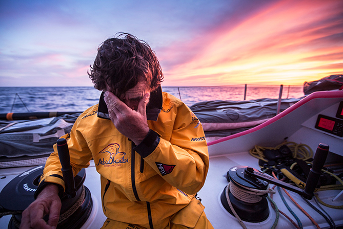 May 5, 2015. Leg 6 Newport onboard Abu Dhabi Ocean Racing. Day 16.  Roberto Bermudez 'Chuny' wipes his eyes backlit by a magnificent sunset over the Atlantic Ocean.