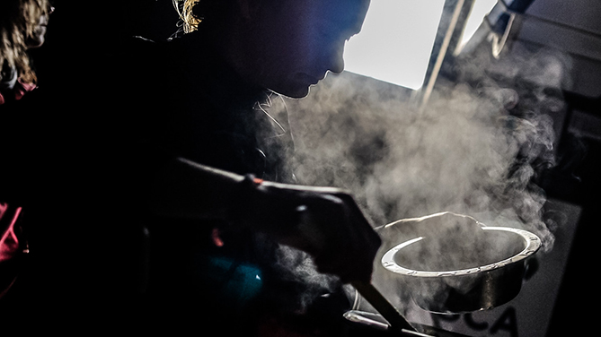August 14, 2014. Round Britain Island Race Day 4 - OBR content Team SCA:  Elodie-Jane Mettraux cooking during the race.