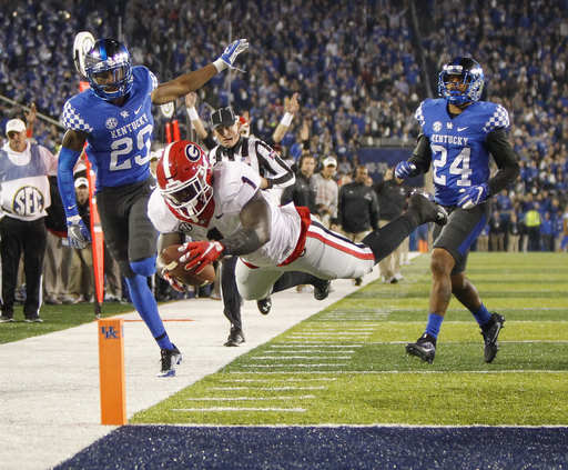 FILE - In this Nov. 5, 2016 file photo, Georgia running back Sony Michel (1) dives into the end zone for a touchdown after getting past Kentucky cornerback Derrick Baity, left, and defensive back Blake McClain, right, during an NCAA college football game