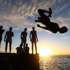 Boys dive off the dock in Porta da Barra in Salvador, Brazil.