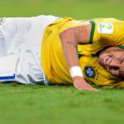 Brazil sensation Neymar writhes on the ground in pain after taking a knee to the back that fractured a vertebra and has ruled him out for the rest of the World Cup.