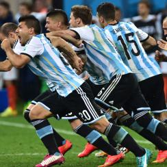 Argentina players rush the field after Maxi Rodriguez's semifinal-clinching penalty kick secures their passage to the World Cup final.