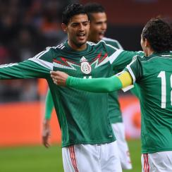 Carlos Vela accepts a congratulatory hug from Andres Guardado after scoring less than eight minutes into his return to the Mexico national team.