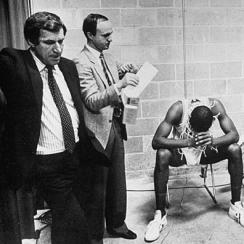 Dean Smith, SID Rick Brewer and players James Worthy (left) and Jimmy Black were the picture of tired, not triumphant, after the Tar Heels won the 1982 NCAA title.