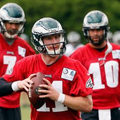 Sam Bradford (7) and Chase Daniel (10) watch Carson Wentz take his reps during practice.