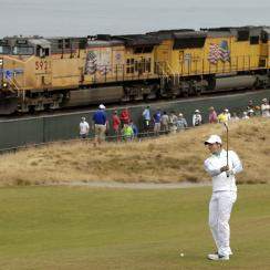 Rory McIlroy prepares to hit from the 16th fairway as a freight train rolls past during the first round.